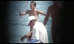 voyeur. skinny female on a public beach. back view