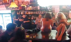 undressed Russian strippers are dancing at the bar stand